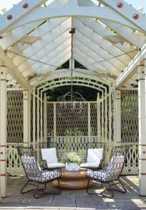 Cream-colored pergola houses four black chairs with white cushions that surround a wood table adored with a white vessel of white flowers