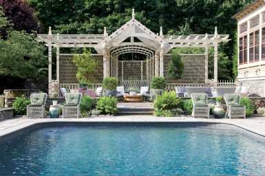 Swimming pool in the foreground with a pergola behind it.