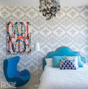 Bedrooms with a colorful blue headboard and a white duvet with blue accent pillows. There's a dark blue chair next to the bed and the wall is covered in gray and white geometric wall paper.