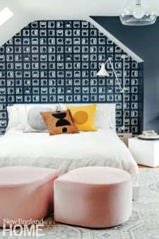 A bed with white coverings against a wall papered with navy and white geometric wall paper