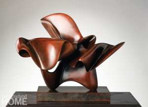 abstract bronze sculpture sitting on wood base