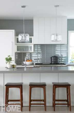 Sterk chose walnut stools with leather tops for a warm counterpoint to the kitchen's cool gray tiles.