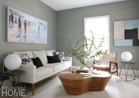The study, with its grasscloth-covered walls and peaceful color scheme, affords a quiet spot for reading. It's also the only room with a TV, which the owners use primarily for viewing tennis matches. A beach scene by Philip Barlow displayed above the sofa nods to summer.