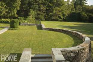 a green lawn surrounded by a stone wall