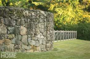 green grass with a stone wall and the pool fence in the background