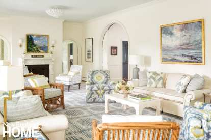 Another shot of the living room with its arched doorways, chairs and sofas in grays, whites and neutrals with a few pops of yellow.