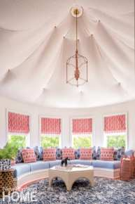 a fabric, tented ceiling in a round room with built-in seating below windows dressed in pink and white roman shades.