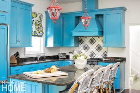 Blue kitchen cabinets with red lanterns hanging above an eat-in island surrounded by blue-and-white French bistro chairs