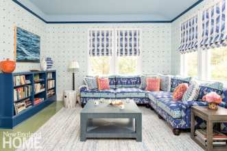 Living room in shades of blue and green. There's wallpaper on the walls, roman shades on the windows and a blue bookcase filled with books. A photo of waves hangs above the bookcase.