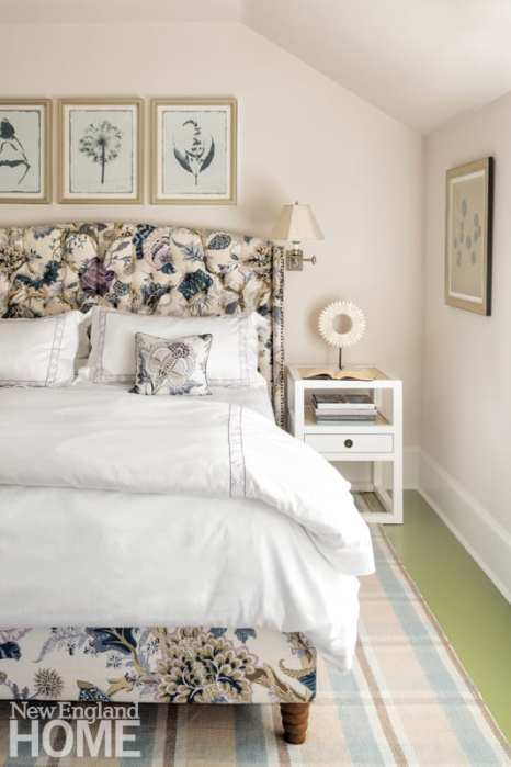 A view of an upholstered bed with white bedding. The floor is painted green.