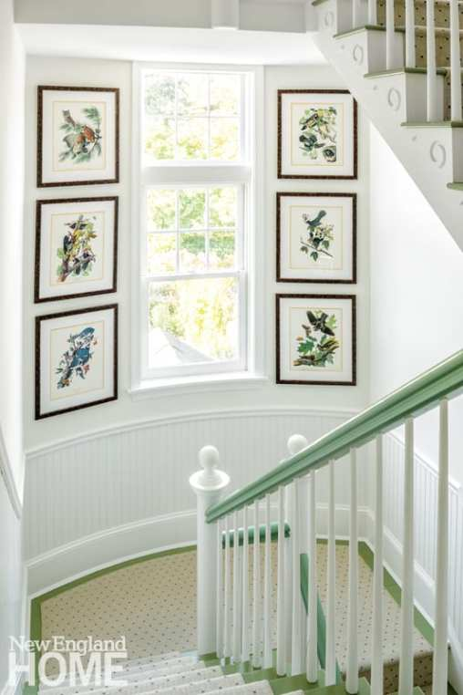 Stairwell with green rails with a window framed with framed bird prints