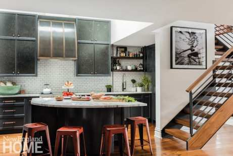 Julian Edelman's kitchen with a marble counter surrounded by red metal stools. There's a staircase off to the right.
