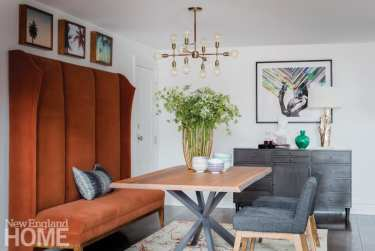 Brown banquette with a tall back in front of a wood and metal table with a gray and wood chair on the opposite side; Julian Edelman's Back Bay Condo