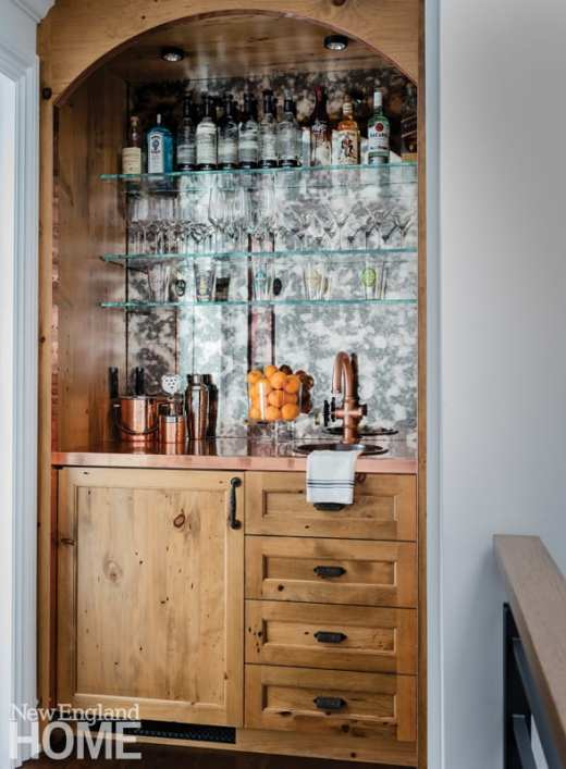 Recessed niche bar stocked with oranges, liquor and copper barware.