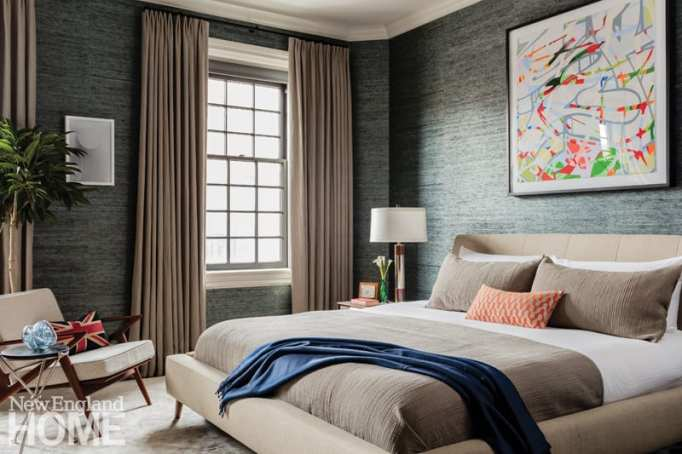 Julian Edelman's bedroom with taupe curtains, denim wallpaper and a bed dressed in neutrals. There's a blue throw at the edge of the bed.
