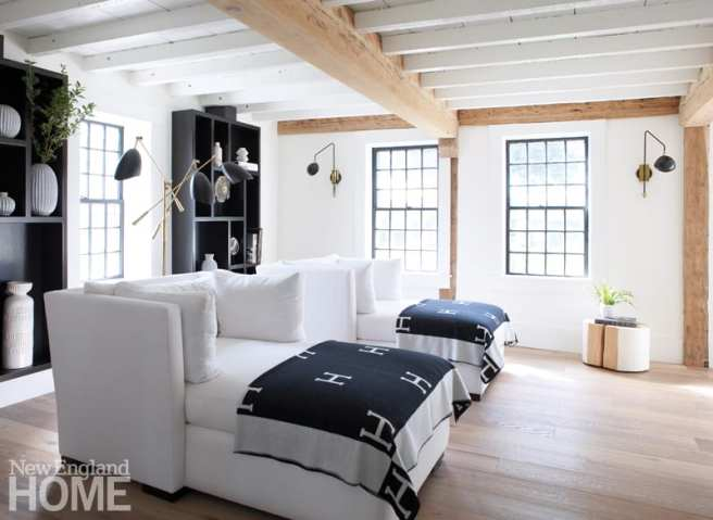 Oversized white chairs adorned with black and white hermes throws. Black shelves display pottery and books.