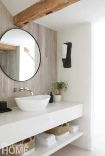 Bathroom with exposed beams and a round mirror above a white porcelain sink