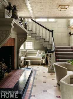 A different view of the fireplace and stairway with a window and couch tucked under the stairs