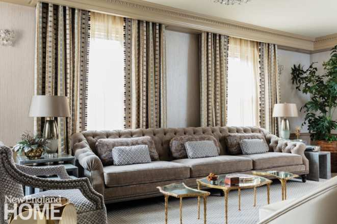 Living room couch in shades of gray. Behind the couch are floor to ceiling windows adorned with drapery.