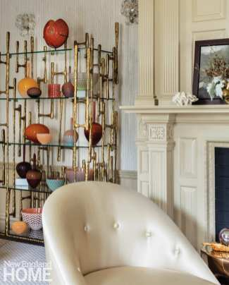 A detail of one of the fireplace pillars with a shelving unit next to it filled with glass vessels in shades of orange and brown