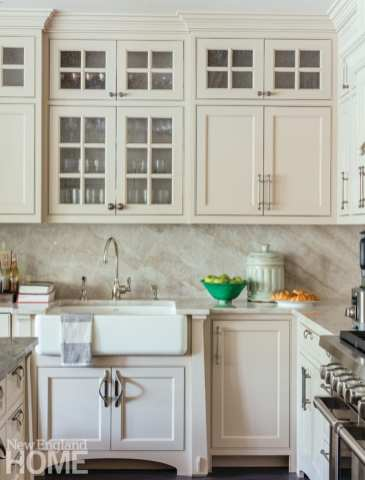 Close-up shot of the kitchen cabinets, which are off-white. There's a white farmhouse sink.
