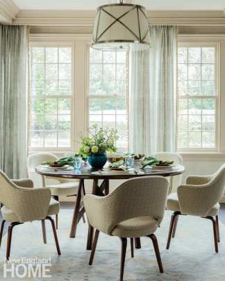 Dining room with round table surrounded by five upholstered chairs. The table is set with plates, napkins and utensils.