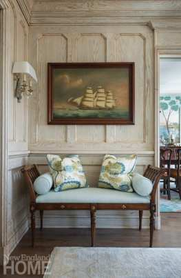 Entryway with bench in front of wood paneled wall. There's a painting of a ship above the bench.
