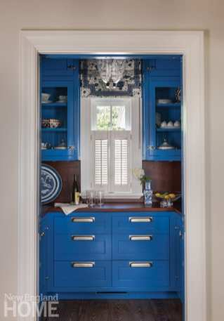 bight blue cabinets with a white shuttered window