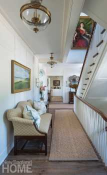 Hallway with carpeted runner and stairs leading on the right. There's a settee on one wall.