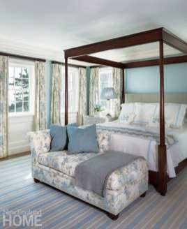 Dark wood canopy bed with a floral covered day bed at its foot