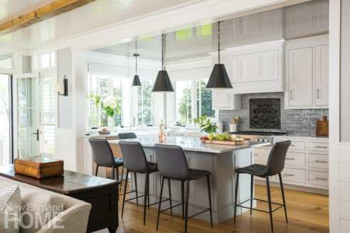 Eat-in kitchen with black bar stools around kitchen island
