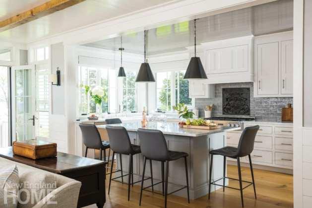 Eat-in kitchen with black bar stools around kitchen island