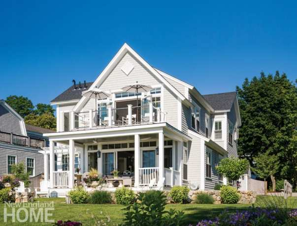 back of the light gray, shingle-style house with a wrap-around porch and second floor patio