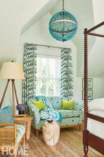 bedroom with dark wood canopy bed and blue beaded chandelier