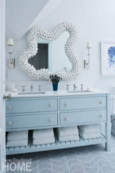 The master bath's barnacle-like mirror frame and wave-patterned floor tiles reference the home's coastal location.