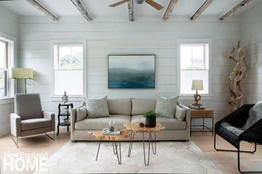 The living room's original ceiling beams were left exposed, brushed with paint, and paired with new beadboard. The art in the house is largely from artists with a local connection, as with the landscape by Truro-based Michael del Visco.