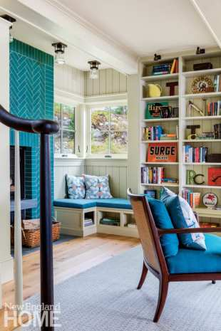bookshelves, window seat and fireplace clad in blue tile