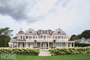 The house is grand, indoors and out, with curved walls, tall windows, numerous gables, and architectural details inspired by the iconic Shingle style.