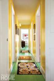 Saturated, vibrant colors and needlepoint rugs line the main hallway.