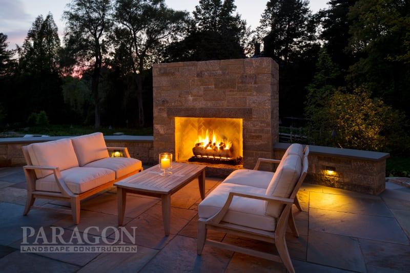 year-round backyard entertaining fireplace at night