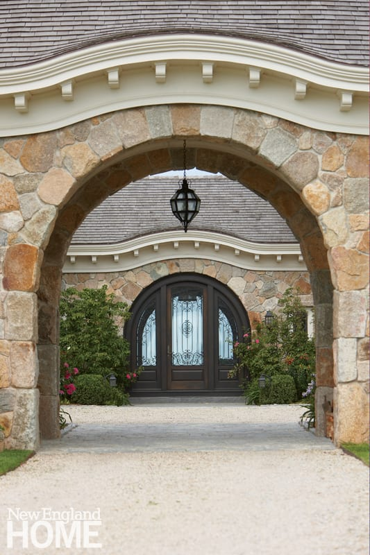 "A handsome fieldstone arch leads to the central courtyard, around which the house is organized. ""This is one of a series of archways that frame specific views, and define how one moves through the house,"" says architect Andrew Reck. The facing door opens into the family's mudroom."