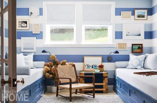 A bunk room with toe-to-toe twin beds on each side is used for lounging or guests. Striped wallpaper, Schoolhouse sconces, and vintage art lend a nautical vibe.