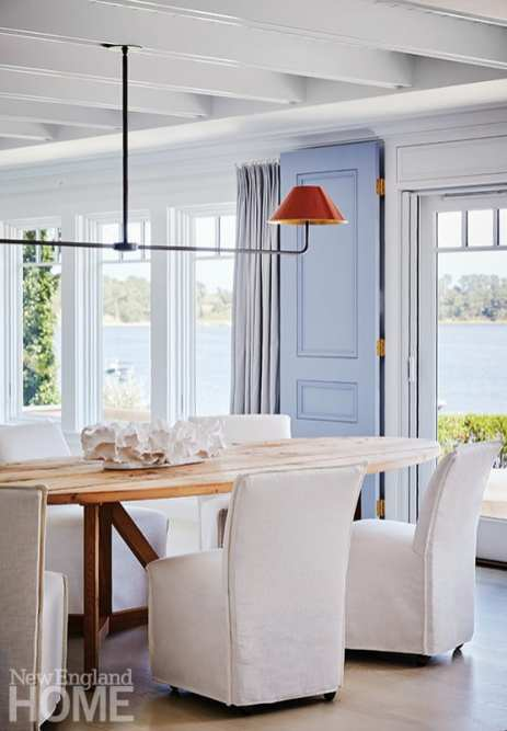 : Tharp chose a custom-built dining table in the shape of a surfboard. It sits near the entrance to the terrace, which is delineated by hydrangea-blue wooden doors, a backbone of the decor's palette.