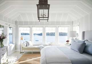 A vaulted ceiling and walls in the second-floor master suite are covered in Schumacher linen upholstery, delivering a delightful canopy effect. Tharp's signature sail-pulley shades dress the windows. The daybed is vintage; Holland & Sherry pillows button up the look.