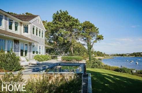 A raised terrace and infinity pool extend into the backyard, which abuts a saltwater pond with views of the bay beyond. Connecting landscaping and hardscaping with the architecture was an important element of the design for Polhemus Savery DaSilva, the firm responsible for the architecture, landscape architecture, and construction of the house.