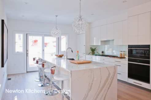 Glamorous lighting adds to the luxurious look of white laquered cabinets.