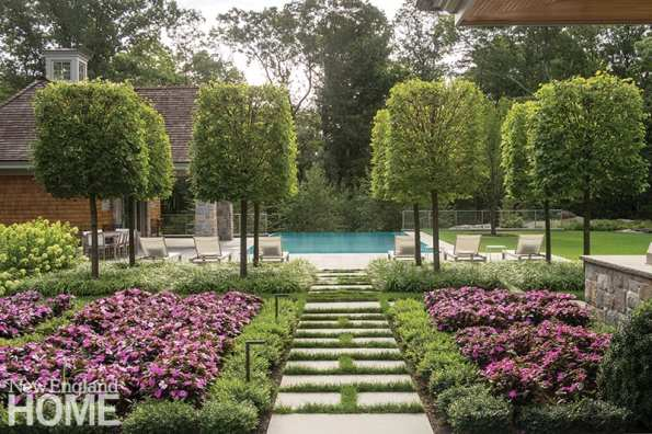 Bluestone pavers and pleached linden trees in neat quadrants create a structured entrance to the pool area. Beneath the trees, liriope blurs the gridded space; impatiens planted en masse add a pop of color. The reflection of the lindens in the pool at night was a delightful consideration.