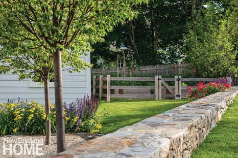 Along the road, Sanni designed a low stone wall hemming the lawn and the post-and-rail-fenced vegetable garden behind the Feake-Ferris House.