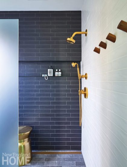 A contrasting black-tile accent wall lends the bathroom a modern feel; clever design concept: an exterior door in the shower leads to an outdoor shower.