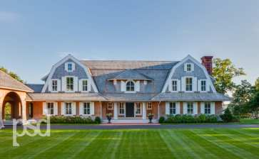 Two classic shingle style gambrel roofs run perpendicular to the main body of the house and flank an entry porch with two robust columns.